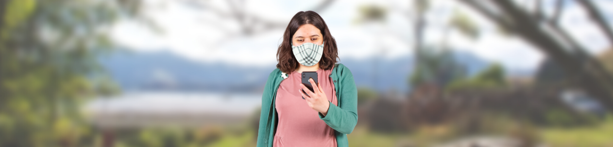 Image of young woman, wearing covid facemask, looking at her mobile phone.