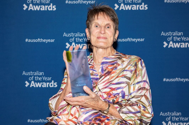 Image of Sue Salthouse holding 2020 ACT State Recipient Senior Australian of the Year award at the Australian of the Year Awards Ceremony. The award is a translucent glass trophy with her name engraved at the base.